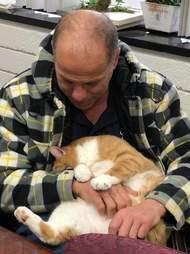 Man cuddling cat in his lap