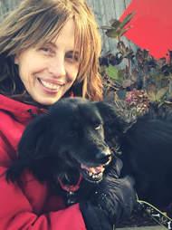 Woman cuddling black dog