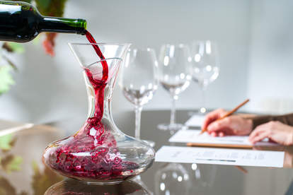 person pouring red wine into decanter