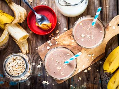 banana smoothie with oatmeal, peanut butter and milk with straw