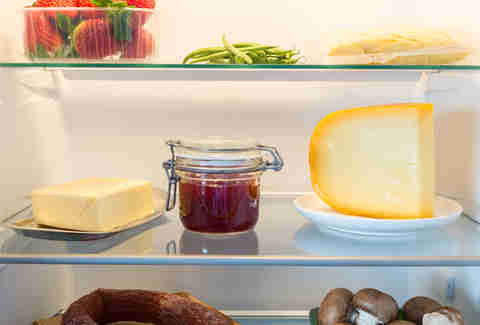 Open fridge filled with cheese and food