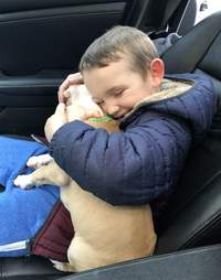 6-year-old Leo snuggles his new adopted puppy