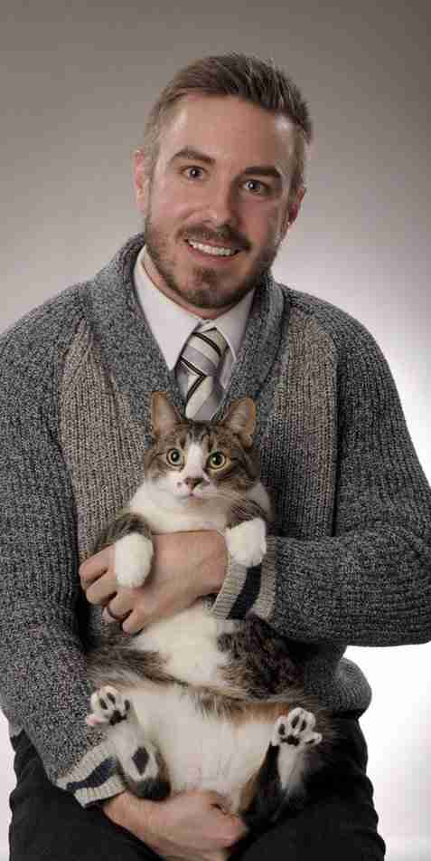 Guy holds cat in graduation photo