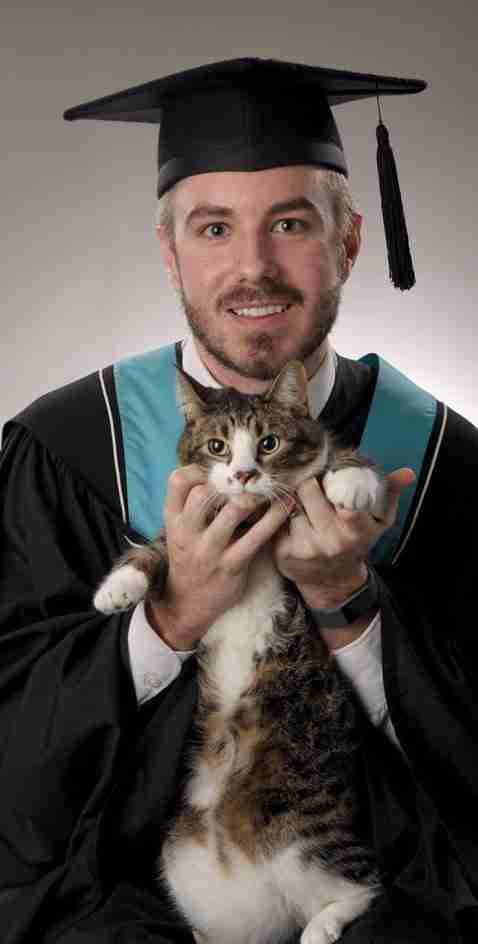Man poses with cat for college portrait