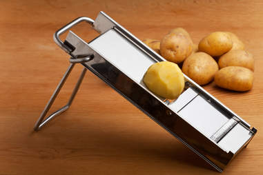 half a potato on a mandolin slicer