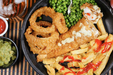 Top down view of an English fish and chips with garden peas, ring onions and mushy peas