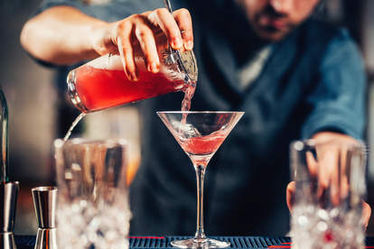 barman pouring cosmopolitan inyo martini glass