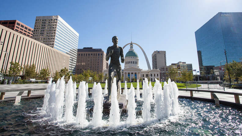 The Runner statue is splashed by the fountain in Kiener Plaza with the Old Courthouse and the Arch framing it in the background.