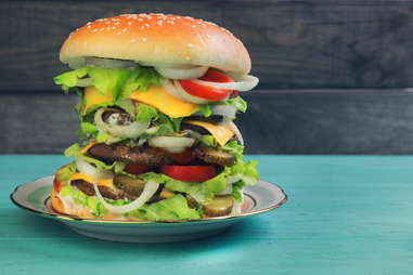 towering burger with many toppings