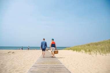 two men walking along a boardwalk toward a beach
