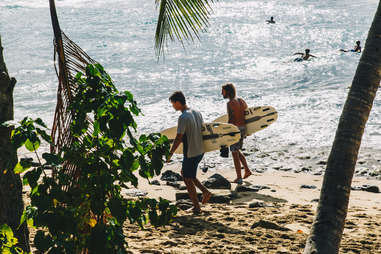 two surfers walking along the beach
