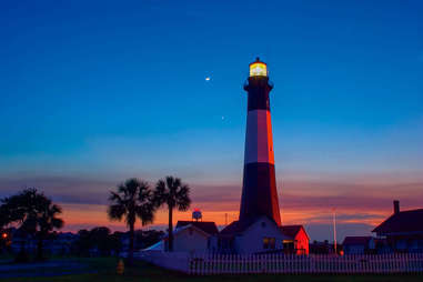 a lighthouse surrounded by palm trees at dusk