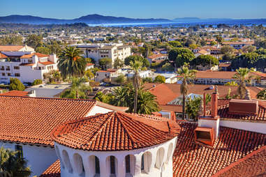 Spanish tile roofs surrounded by palm trees looking out toward the ocean