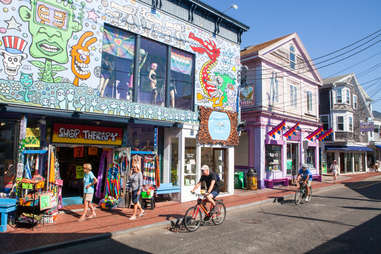 people biking and walking in front of colorful shops on a main street