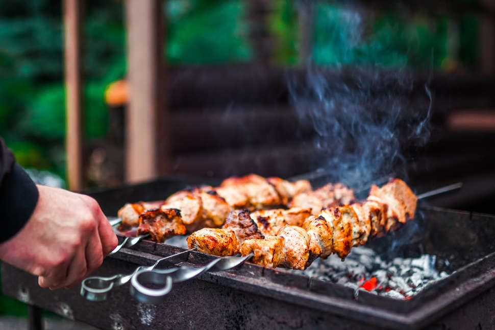 Grilled kebab cooking on metal skewer
