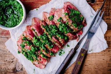 grilled barbecue beef steak with green chimichurri sauce