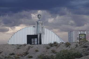 a giant alien statue in front of an aircraft hangar
