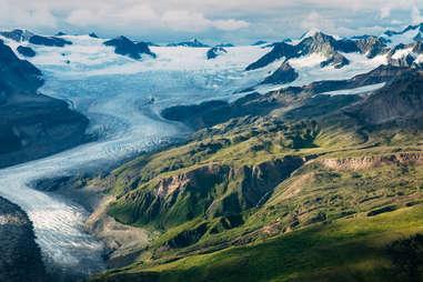an enormous glacier near green mountains