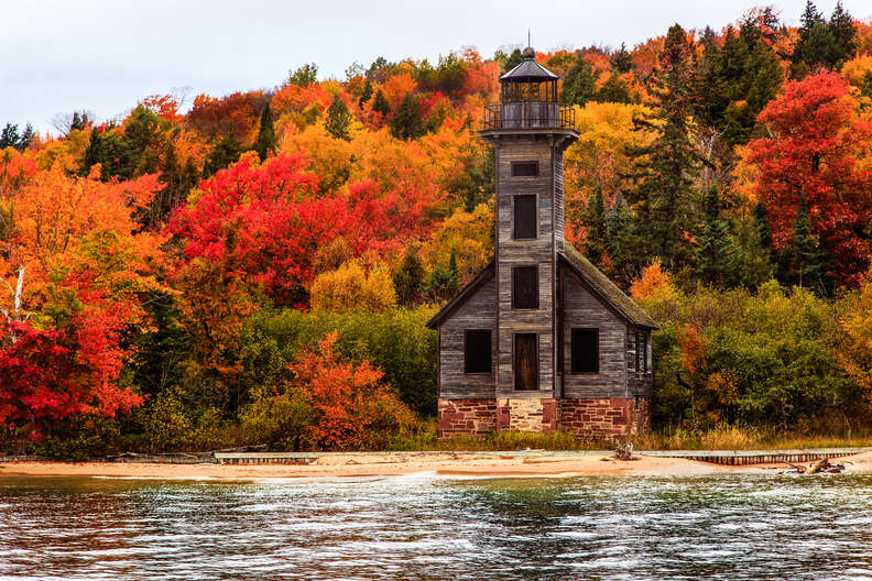a wooden lighthouse on a lakefront in fall