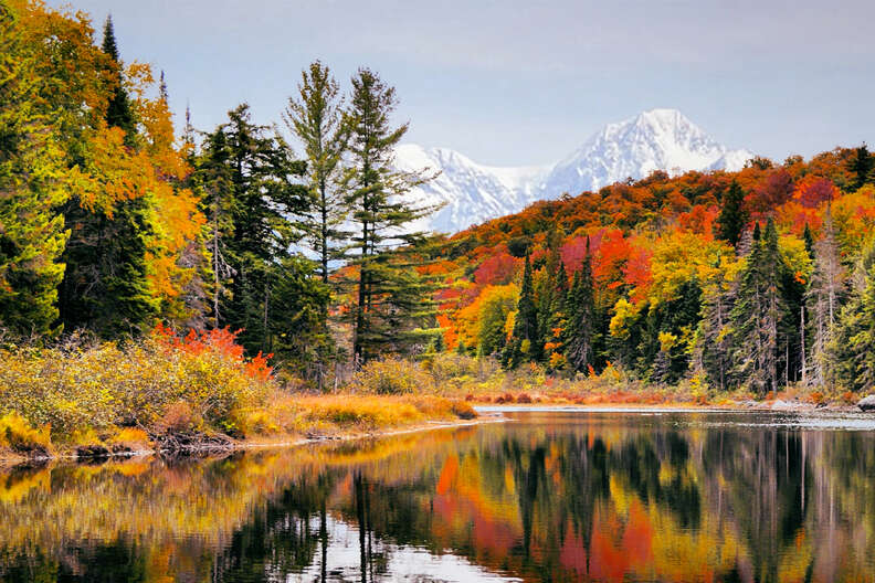 a lake surrounded by colorful trees in fall with a mountain range in the distance