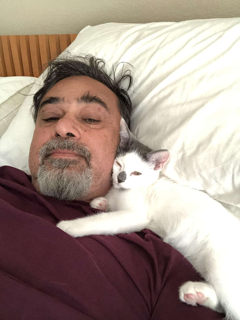 Cat snuggled against man's neck