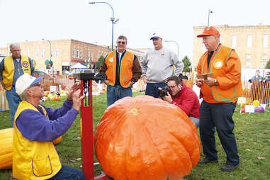 people weighing a giant pumpkin