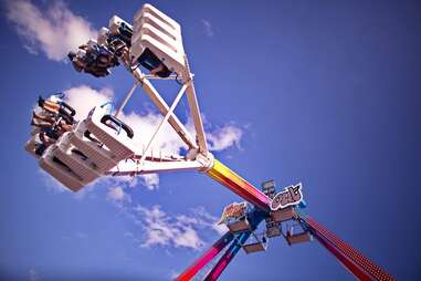 people riding a spinning carnival ride