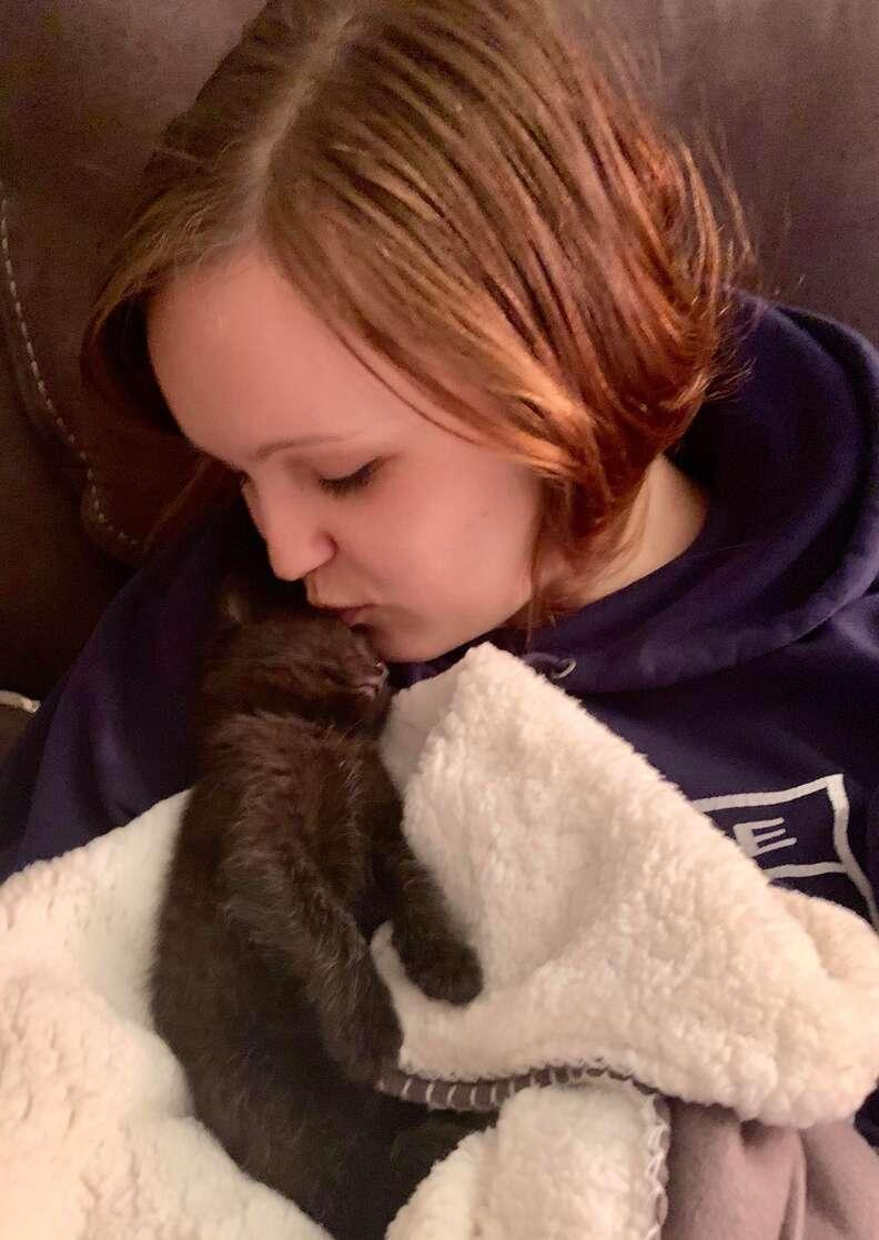cat carries around blanket
