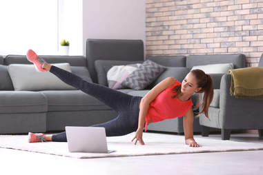 A woman works out in her living room