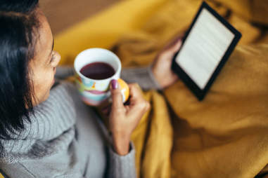 A woman reads on an electronic device