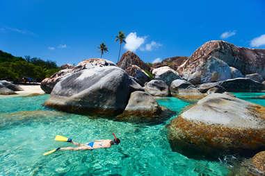 a woman snorkeling in clear water between the rocks of Virgin Gorda, British Virgin Islands, Caribbean