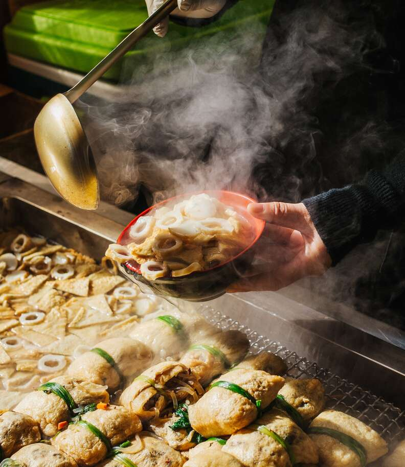 a person holding out a bowl of steamy fish cakes in Busan, Korea