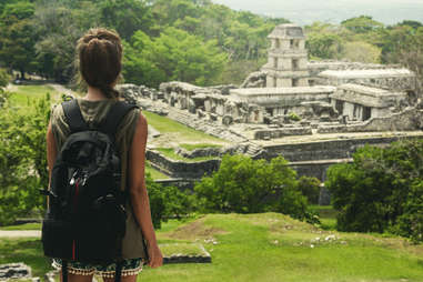 a woman backpacker overlooking the Ancient Mayan ruins of Palenque in Chiapas, Mexico
