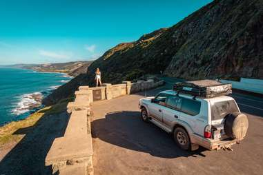 woman and a car standing on a seaside road on the Great Ocean Road, Anglesea Victoria, Australien
