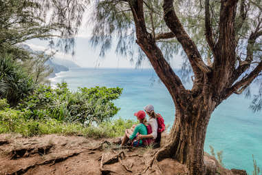 two women sitting beneath a tree on a cliff near the ocean