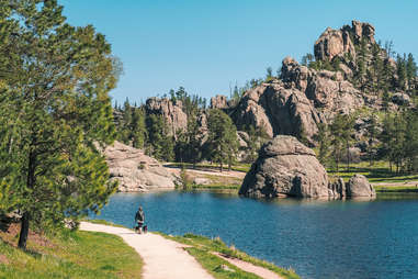 a person walking on a trail next to a lake surrounded by large stacked rocks