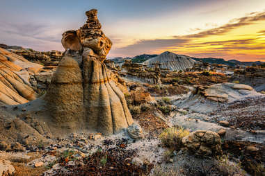 a large desert with brush and strange hoodoo rock formations