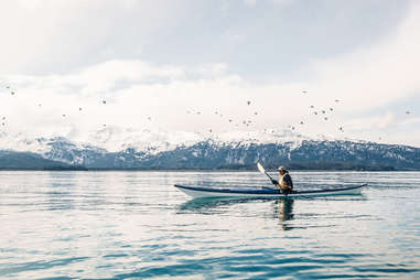 person canoeing in a lake surrounded by snowy mountains