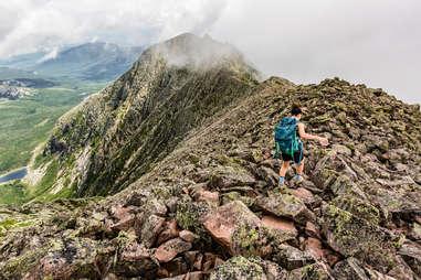 person hiking along a craggy mountaintop