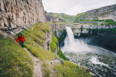 person hiking along the edge of a cliff with a waterfall nearby