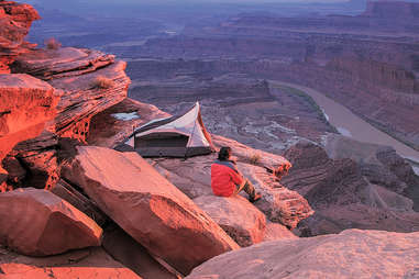 a person camping on a cliff above a rocky river canyon