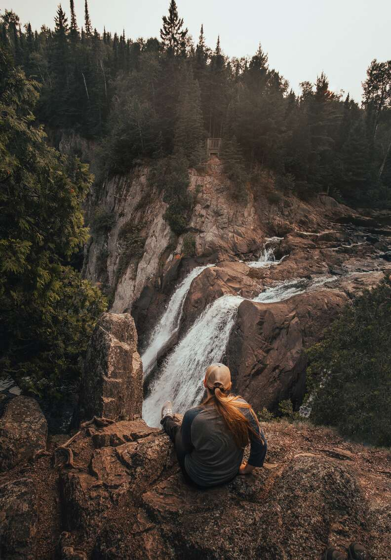 woman sitting in front of a waterfall