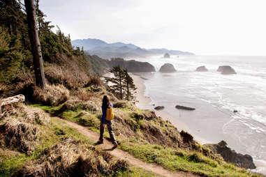 person walking along a trail above a beach