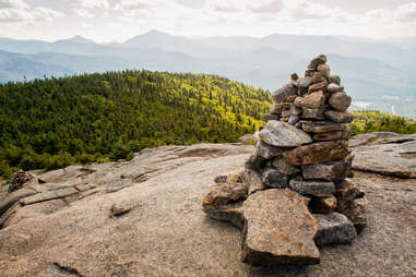 a stack of rocks overlooking a forest and mountains