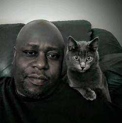 Animal rescuer Calvin Tucker poses with his cat Henry