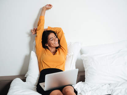 A woman sits up in bed, smiling with a laptop computer