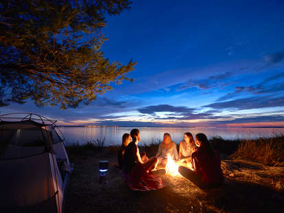 friends around a campfire on a lake