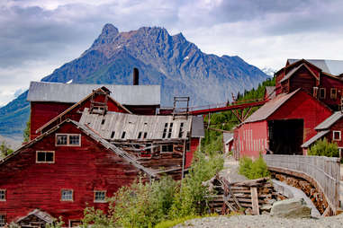 a rickety red mining town in front of a mountain