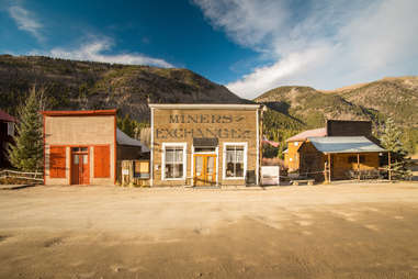 store fronts in an abandoned desert town with mountains in the background