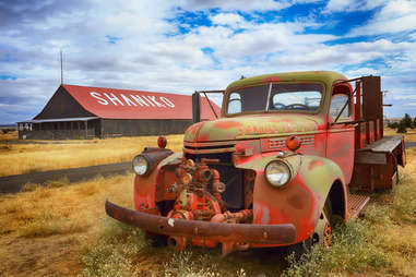 a rusting red truck in front of a farmhouse